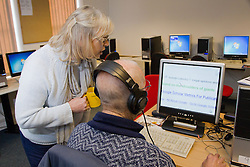 Computer class for people with visual impairments - volunteer with man using headphones for audio and enlarged text.