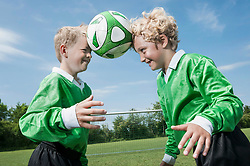 Two junior soccer players learning ball control