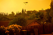 A firefighting helicopter battling the Carr Fire goes to refill its water at Falks Lake, Friday, July 27, 2018, in Redding, Calif. The Carr Fire that burned into Redding grew to 80,900 acres — around 125 square miles — and was only 5 percent contained as of Saturday morning, according to Cal Fire. Two firefighters have died in the blaze.