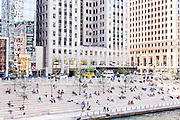 People relax along the Riverwalk near Wacker Drive and North Clark Street on a summers day in Chicago, Illinois, USA