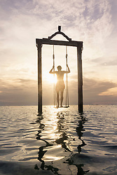 Young man standing on rope swing at beach against sunset, Gili Trawangan, Lombok, Indonesia