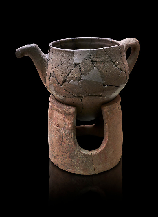 Hittite terra cotta teapot with strainer spout on a charcoa; burner base  . Hittite Period, 1600 - 1200 BC.  Hattusa Boğazkale. Çorum Archaeological Museum, Corum, Turkey. Against a black bacground. .<br />  <br /> If you prefer to buy from our ALAMY STOCK LIBRARY page at https://www.alamy.com/portfolio/paul-williams-funkystock/hittite-art-antiquities.html  - Type Hattusa into the LOWER SEARCH WITHIN GALLERY box. Refine search by adding background colour, place,etc<br /> <br /> Visit our HITTITE PHOTO COLLECTIONS for more photos to download or buy as wall art prints https://funkystock.photoshelter.com/gallery-collection/The-Hittites-Art-Artefacts-Antiquities-Historic-Sites-Pictures-Images-of/C0000NUBSMhSc3Oo