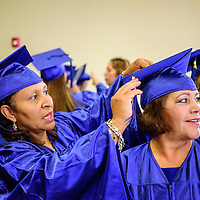 060515  Adron Gardner/Independent<br /> <br /> Theresa de Jesus Woods, left, attaches the cap tassel for Virginia Espino before the New Life Learning GED program graduation at the Lighthouse Church in Gallup Friday.
