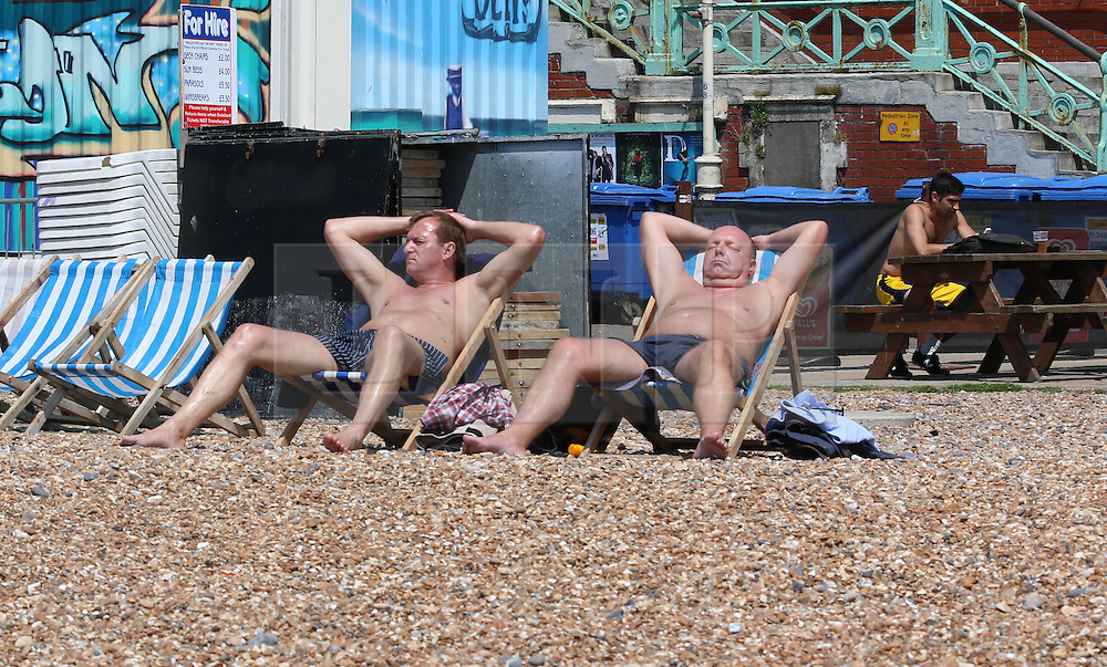 © Licensed to London News Pictures. 13/06/2014. Brighton, UK. Men sunbathing on Brighton beach. Today, Friday 13th June is expected to be the hottest day of the year so far with temperatures hitting nearly 30C at some locations. Brighton beach is slowly filling up with sunbathers and people wanting to relax by the beach. Photo credit : Hugo Michiels/LNP