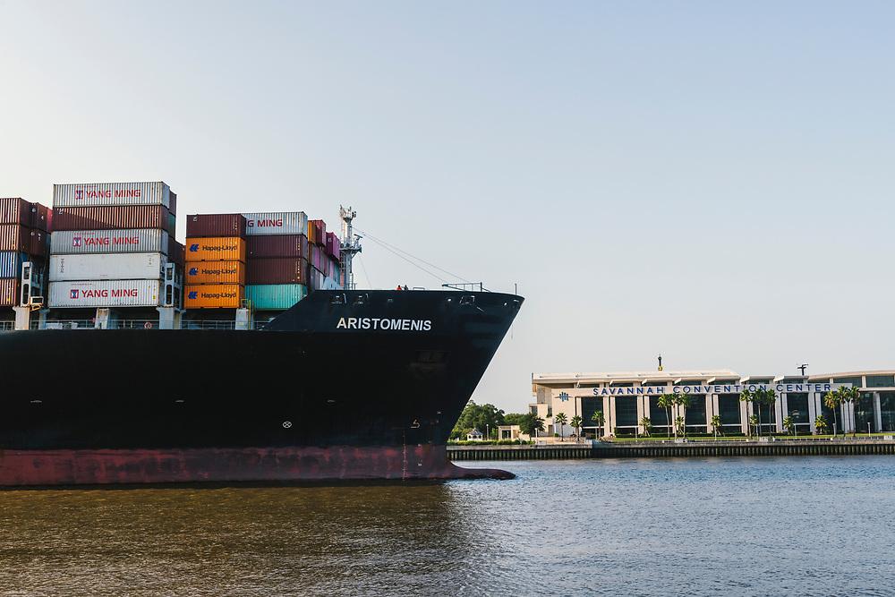 Savannah, Georgia, USA - July 29, 2021: A container ship called Aristomenis departs the deep water port of Savannah, sailing past the Savannah Convention Center.