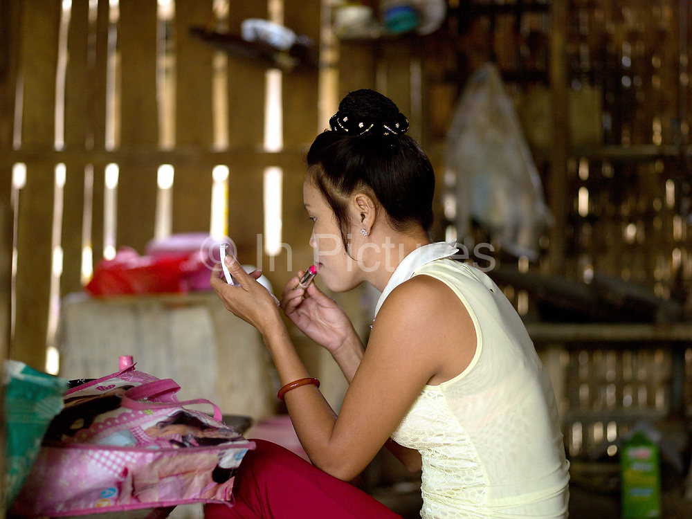 A Vietnamese prostitute applies lipstick at home in Ban Pakpok, Phongsaly province, Lao PDR. Ban Pakpok is small collection of houses recently relocated near to the Nam Ou river due to the Nam Ou Cascade Hydropower Project Dam 5. It is the closest habitation to the dam construction site, the local people rent rooms to the prostitutes who provide services to the Chinese construction workers.
