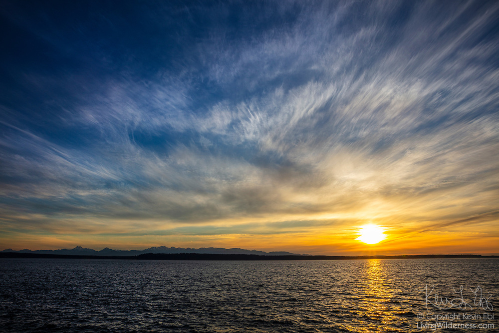 Two layers of clouds, high cirrus and mid-level altocumulus, fill the sky over Puget Sound and the Olympic Mountains in this view from Edmonds, Washington.