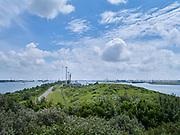 View on the small piece of land with road and windturbines which devides the canal Nieuwe Waterweg near the port of Rotterdam, Netherlands - Uitzicht op de Nieuwe Waterweg en windmolens voor windenergie bij Hoek van Holland en Rozenburg.