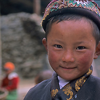 A village boy, probably of Memba descent, stands in his village the in Lunang Valley, of Tibet, China.