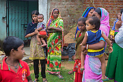Holding a toddler, Tabasum Khatun, 14, is standing next to her mother, Kitabun Bibi, 45, (centre) and other women in Algunda village, pop. 1000, Giridih District, rural Jharkhand, India.