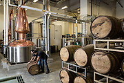 Vishal Gauri and Virag Saksena (right) roll a whiskey barrel at 10th Street Distillery in San Jose, California, on September 4, 2019. (Stan Olszewski for Content Magazine)