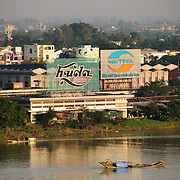 A boat heads down the Perfume River in front of some of the large advertising signs that line the western bank of the Perfume River in Hue, Vietnam.