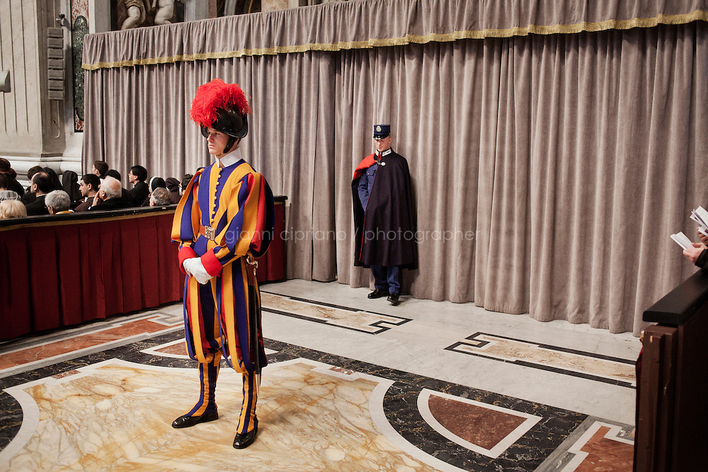 VATICAN CITY - 12 MARCH 2013: (L-R) A Swiss guard and a Vatican gendarme monitor Saint Peter's Basilica during the Pro Eligendo Pontifice Mass, or the Mass for the Election of the Roman Pontiff, with the 115 cardinals that will elect the new Pope, in Vatican City, on March 12, 2013...After the mass, 115 cardinals are set to enter the conclave to elect a successor to Pope Benedict XVI after he became the first pope in 600 years to resign from the role. The conclave will take place inside the Sistine Chapel and will be attended by 115 cardinals as they vote to select the 266th Pope of the Catholic Church.