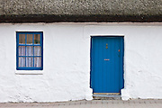 Blue and white traditional whitewashed thatched cottage in Ardmore Village, County Waterford, Ireland