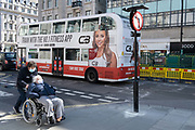 A carer pushes a woman past a London bus adorned with an ad for health and fitness, on Oxford Street, during the third lockdown of the Coronavirus pandemic, on 29th March 2021, in London, England.
