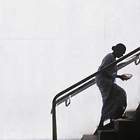 Sri Lanka, Silhouette of female worshipper carryling alms bowl at Buddhist shrine climbs sunlit stairs.