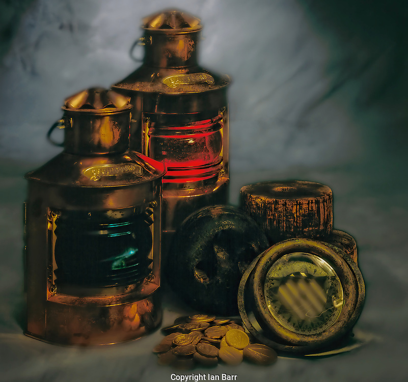 A moody image of antique Navigational Lanterns,Pot and Starboard, with an old ships floating Compass,Cork float Block and old gold coins.