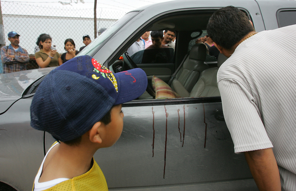 Reynosa, Tamaulipas - 17 Feb 2009 - .Bystanders look at a blood-splattered, bullet-riddled Chevrolet SUV on the side of Boulevard Miguel Hidalgo in Reynosa after a shootout on Tuesday afternoon..Photo by Alex Jones / ajones@themonitor.com