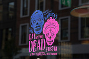 "Day of the Dead promotion in a restaurant window following a suspected outbreak of norovirus, several branches of the Wahaca Mexican food chain were closed after over 350 members of the public and staff fell ill of a probable breakout of the winter vomiting bug, including this branch in Great Portland Street in London, United Kingdom. Co-founders Thomasina Miers, and Mark Selby, said: ""We assessed each case and when it became clear they were not isolated incidents, we got in touch with relevant officials at Public Health England and environmental health officers."" In all nine branches were suspected and closed, and four have reopened as of 3rd November 2016."