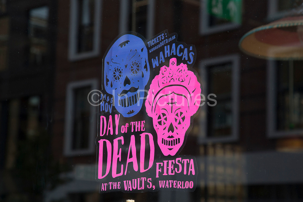 """Day of the Dead promotion in a restaurant window following a suspected outbreak of norovirus, several branches of the Wahaca Mexican food chain were closed after over 350 members of the public and staff fell ill of a probable breakout of the winter vomiting bug, including this branch in Great Portland Street in London, United Kingdom. Co-founders Thomasina Miers, and Mark Selby, said: """"We assessed each case and when it became clear they were not isolated incidents, we got in touch with relevant officials at Public Health England and environmental health officers."""" In all nine branches were suspected and closed, and four have reopened as of 3rd November 2016."""