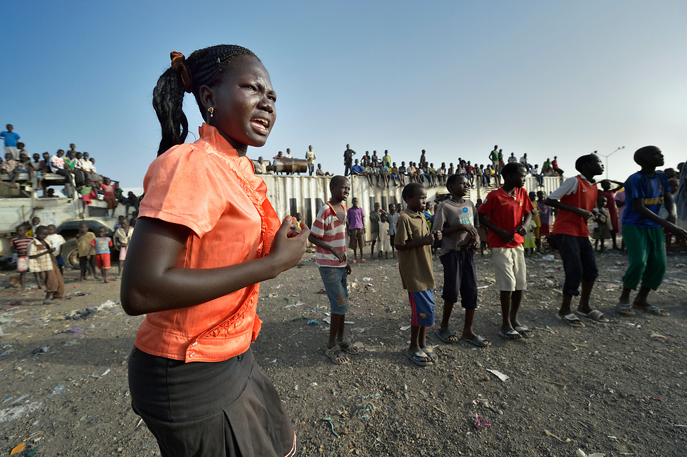 A girl displaced by war participates in a church-sponsored dance group inside a United Nations base in Malakal, South Sudan. More than 20,000 civilians have lived inside the base since shortly after the country's civil war broke out in December, 2013, and renewed fighting in 2015 drove an additional 5,000 people into the safety of the camp. The dance group is sponsored by the Catholic community that operates inside the camp.
