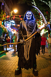 © Licensed to London News Pictures . 27/10/2018. Manchester, UK. A man dressed as the grim reaper , with effects inspired by a jewel-encrusted skull design by Damien Hirst , on Canal Street in Manchester City Centre . Revellers on a night out , many in fancy dress , on the weekend before Halloween . Photo credit: Joel Goodman/LNP