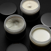 Pete and Pedro hair care jars with tops open showing contents.