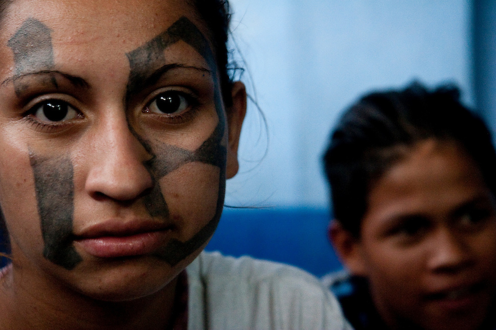 Jackelin Martinez Gusman (left) and Luis Martinez Armas (right) wait at the Ilopango police station to be transferred to the minor's and woman's prison in San Salvador. Jackelin is 19 and a recent mother. She and her husband has been in the 18th street for years. They were both brought in to the station for extortion.  Luis is 16 and was picked up for associating with a gang . He has been in 18th street for three years.
