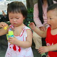 Asia, China, Chongqing. Young boy wants to play with girl blowing bubbles at the park.