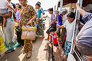 """17 JUNE 2013 - YANGON, MYANMAR:  Passengers disembark on the Dala side of the Yangon-Dala Ferry. The ferry to Dala opposite Yangon on the Yangon River is the main form of transportation across the river. Every day the ferry moves tens of thousands of people across the river. Many working class Burmese live in Dala and work in Yangon. The ferry is also popular with tourists who want to experience the """"real"""" Myanmar. The rides takes about 15 minutes. Burmese pay about the equivalent of .06¢ US for a ticket.  Foreigners pay about the equivalent of about $4.50 US for the same ticket.   PHOTO BY JACK KURTZ"""
