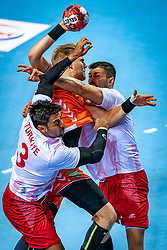 The Dutch handball player Patrick Miedema and Alp Eren Pektas, Ugur Erceylan in action during the European Championship qualifying match against Turkey in the Topsport Center Almere.