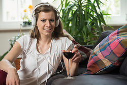Portrait of a young woman listening to music and drinking wine in living room, Munich, Bavaria, Germany