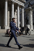 A stylish businessman in a shiny blue suit strides below the classical architecture of Royal Exchange and the WW1 war memorial at Bank Triangle, on 10th May 2017, in the City of London, England.