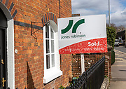 Estate agent property sold sign outside red brick historic house, Marlborough, Wiltshire, England, UK