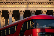 Latin inscriptions on the pediment of the Royal Exchange Passengers look from the front seats of their London bus in the City of London, the capital's financial district, on 27th February 2021, in London, England. At the top of Doric and Ionic columns with their ornate stonework, powerfully strong lintels cross, bearing the load of fine artistry and carvings which feature the design by Sir William Tite in 1842-1844 and opened in 1844 by Queen Victoria whose name is written in Latin (Victoriae R). It's the third building of the kind erected on the same site. The first Exchange erected in 1564-70 by sir Thomas Gresham but was destroyed in the great fire of 1666. It's successor, by Jarman, was also burned down in 1838. The present building is grade 1 listed and cost about £150,000.