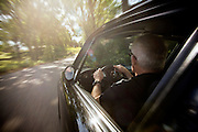 Image of a older man driving a real 1973 Porsche 911 RS Carrera in motion on a country road in California, model and property released by Randy Wells