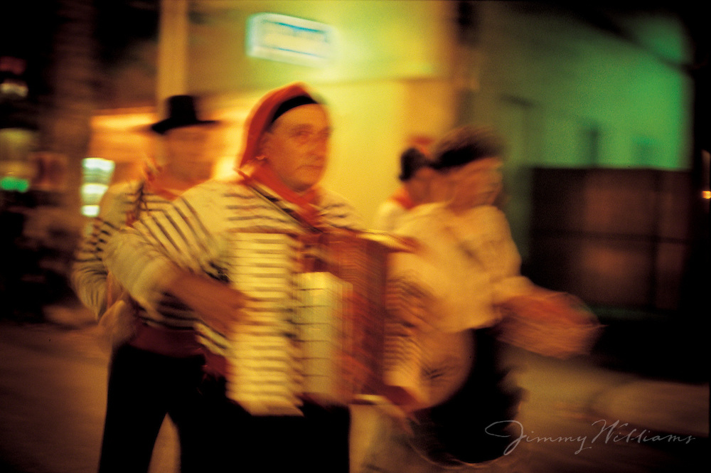 A group of men playing music entertain as they walk down the street in an Italian town