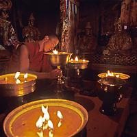 CHINA, TIBET.  Tibetan Buddhist monk tends yak butter lamps at Samye Monastery, one of oldest in Tibet.
