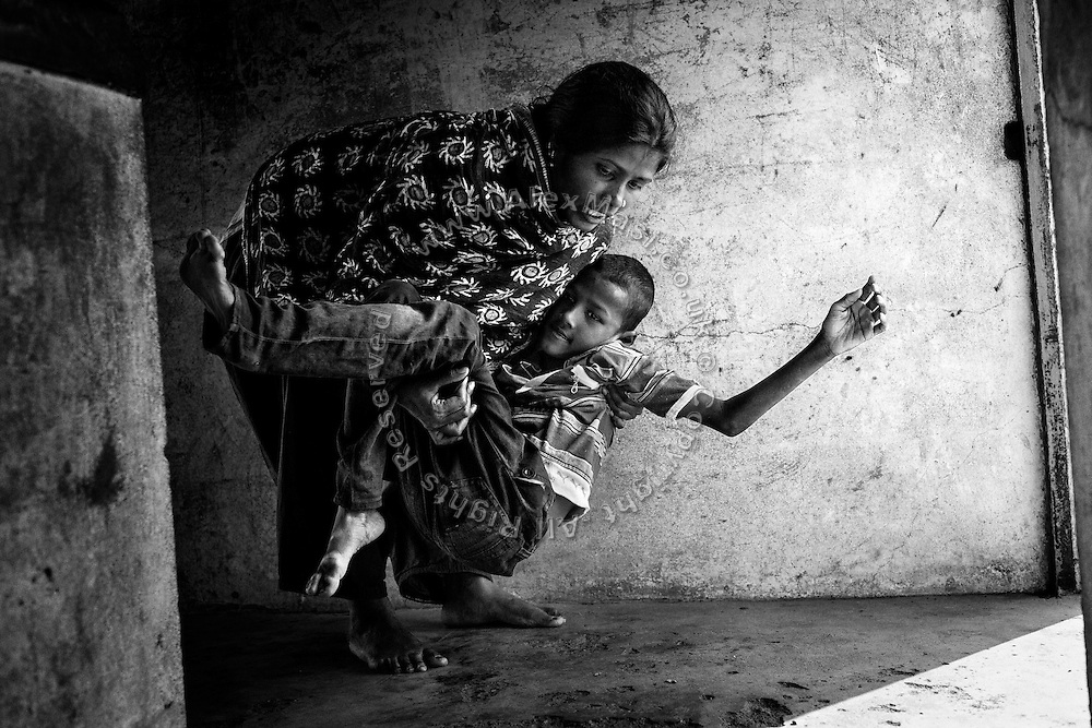 Ashia, 31, a '1984 Gas Survivor', is lifting her disabled son Anas, 11, a boy affected by severe cerebral palsy, while inside their home in Aishbag Colony, Bhopal, Madhya Pradesh, central India.
