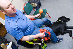Visually impaired man with his guide dog playing the tambourine during a drumming workshop at the NRSB activity day at their centre on Ortzen Street,  This is part of the IMPACT project; an interactive road show delivering a series of events designed to give the visionimpaired community of Nottinghamshire the opportunity to IMPACT on the future of Notts Royal Society for the Blind,