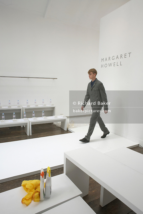 """A male model starts his walk on the catwalk of couturier Margaret Howell's Fashion Week show rehearsal in the company's retail flagship and design studio at 34 Wigmore Street, Central London England. With a duster and spray cleaning agent in the foreground, the young man walks, as if having emerged through the wall. Bottles of bottled mineral water await their users but the fashion show's audience have yet to arrive. Howell is one of Britain's more understated of couture brands alongside more flamboyant personalities. Howell admits to being """"inspired by the methods by which something is made .. enjoying the tactile quality of natural fabrics such as tweeds, linen and cotton in a relaxed, natural and lived in look."""""""