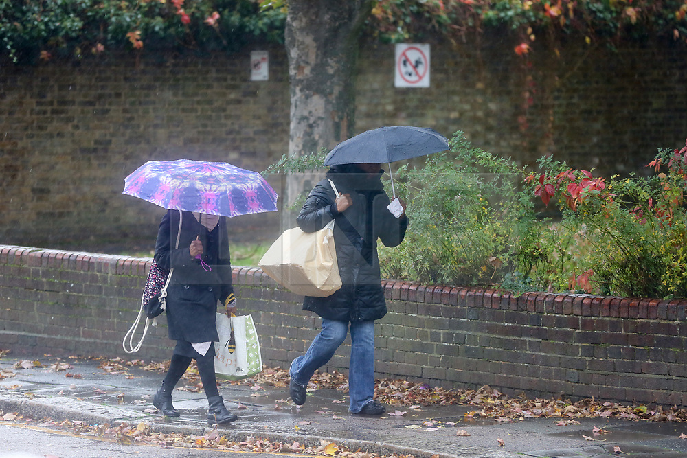 © Licensed to London News Pictures. 31/10/2020. London, UK. Women shelter from rainfall underneath an umbrella in north London. Met Office has issued weather warnings from today to Monday for heavy rainfall and strong winds from Storm Aiden and the remnants of Hurricane Zeta. Photo credit: Dinendra Haria/LNP