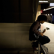 A man plays the guitar while waiting for the subway train in Los Angeles.