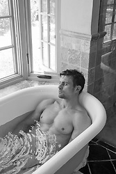 man in a bathtub looking out the window