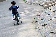 view from behind of boy riding bike with training wheels