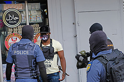 JOHANNESBURG, SOUTH AFRICA - APRIL 18: SAPS officers question a man during a South African Police Service (SAPS) Metro Police and Army supported patrol in Rockey Street, Yeoville. Random searchs and social distancing measures on April 18, 2020 in Johannesburg South Africa. Under pressure from a global pandemic. President Ramaphosa declared a 21 day national lockdown extended by another two weeks, mobilising goverment structures accross the nation to combat the rapidly spreading COVID-19 virus - the lockdown requires businesses to close and the public to stay at home during this period, unless part of approved essential services. (Photo by Dino Lloyd)