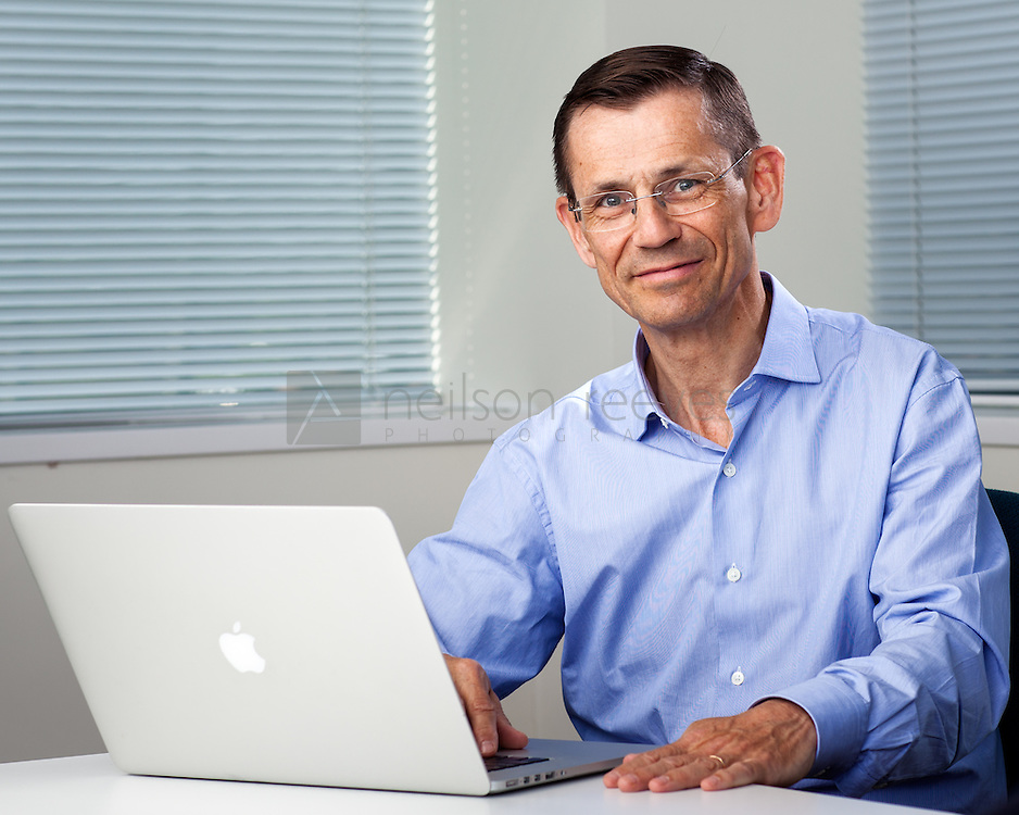 Corporate portrait businessman in office sat at desk with Mac Pro Laptop in foreground