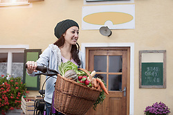 Mid adult woman with bicycle and vegetables standing in front of wholefood shop, Bavaria, Germany