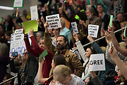 Citizens hold up signs while a question is being asked towards U.S. Rep. Michael C. Burgess during a town hall meeting within his district at Flower Mound Marcus High School in Flower Mound, Texas on March 4, 2017.  (Cooper Neill for The Texas Tribune)