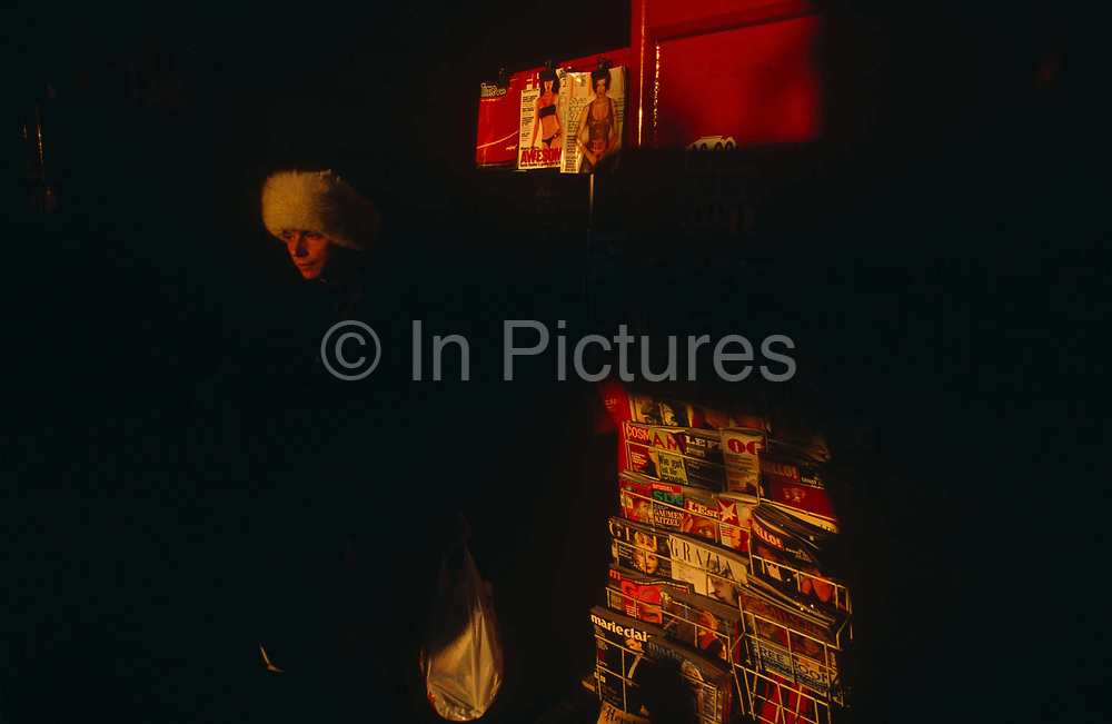 In late afternoon winter sun, a lady emerges from deep shadow wearing a fur hat on the Kings Road in Chelsea, London, England. Foreign magazines line a rack of an outdoor newsagent and we only see the lady's head in the sunlight. There is a low colour temperature orange glow to the picture and only the lady's face wrapped in a fur hat and the magazine covers can be seen in detail. There are few highlights apart from the magazines in the sun, and more shadow area making this a dark image. The Kings Road has been famous in London since the 60s when fashion and flower power was the label most associated with being young and hip in the Swinging Sixties. It is more sober these days but families and young people tend to be wealthier, white and middle-class than other areas such as Carnaby Street which is seen as seedy and cheap.